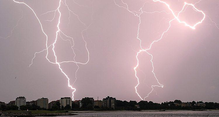 Flera stora blixtar slår ner i marken.