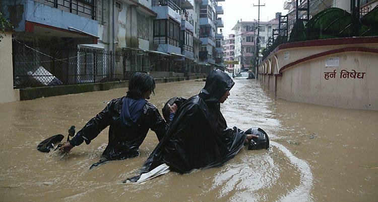 Två personer vadar fram med vatten upp till midjan mitt inne i staden Katmandu.