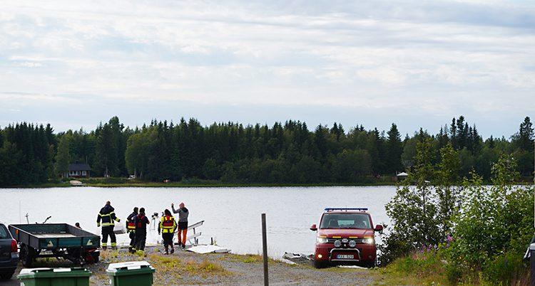 Personal och bilar från räddningstjänsten står vid en strand.