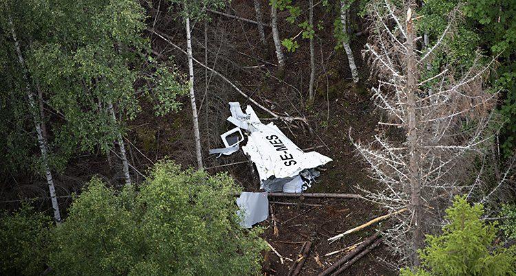 Bild tagen från luften på olycksplatsen. Mellan träden syns en del av det vita planet som är illa åtgånget.