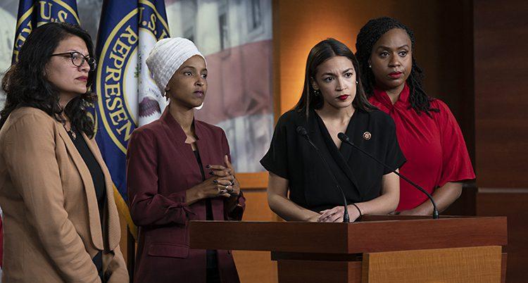 Fyra kvinnliga politiker står på en scen och pratar med journalister.