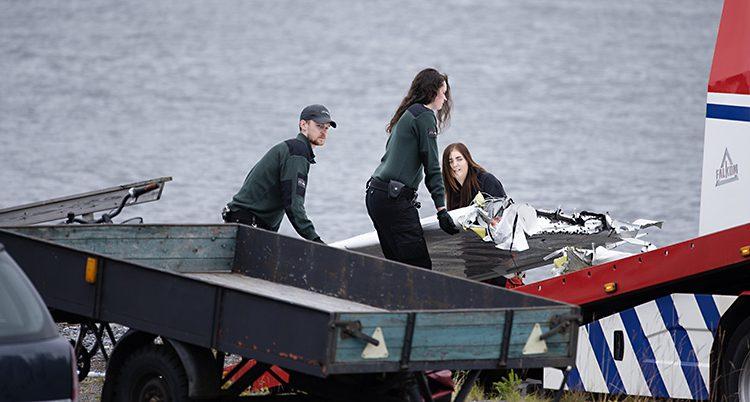Tre personer med mörkgröna vakt-tröjor lyfter upp en del av vingen som ser ut att ha brutits av.