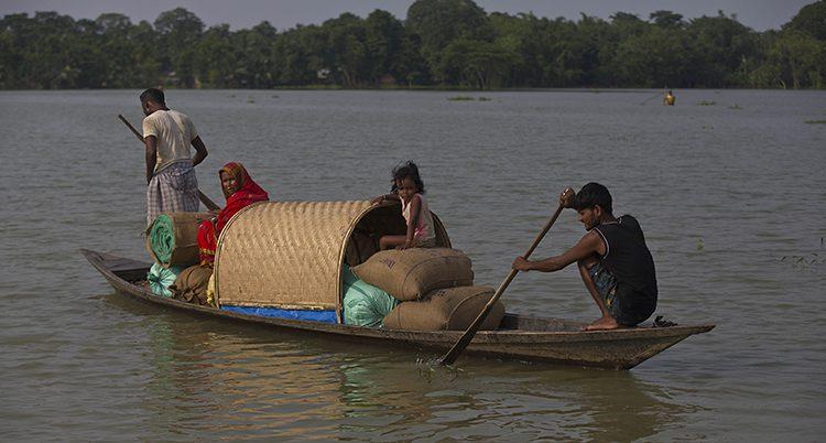 En låg kanotliknande båt med en hel familj och packning på.