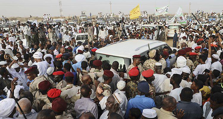 Massor av människor samlade. Taket av en bil syns mellan människorna.