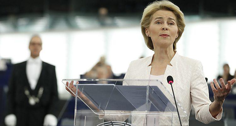 van der Leyen i vitt framför en talarstol. Hon ser nöjd ut.