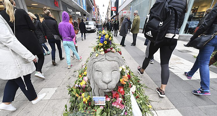 Människor går förbi ett lejon i betong. Det ligger en massa blommor runt lejonet.