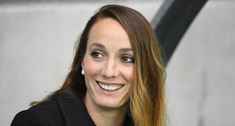 Fotbollsspelaren Kosovare Asllani ler och tittar åt sidan. Hon har en svart tröja på sig.