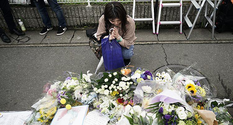En kvinna knäböjer framför en hög med blombuketter på en trottoar.
