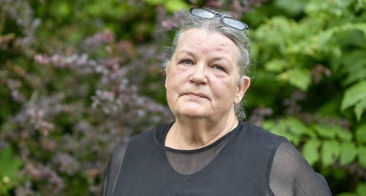 Elisabet Nilsson står med svarta kläder. I bakgrunden syns träd och blad.
