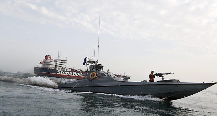 En svart militärbåt syns framför en större båt med texten Stena.