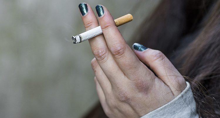 En hand med grönt nagellack håller en cigarett