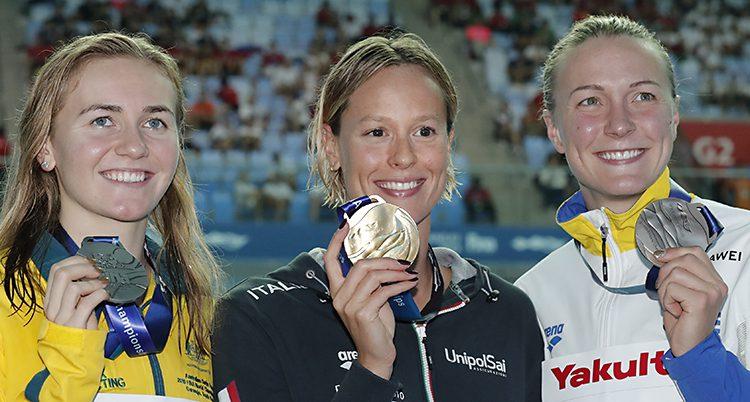 Tre simmare håller upp sina medaljer efter ett lopp.