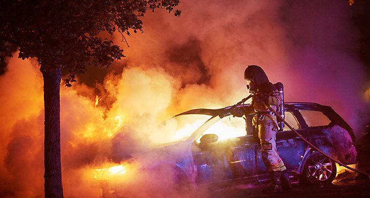 Rök och eld kommer från bilen. En brandman sprutar vatten.