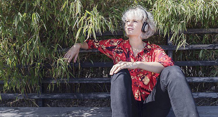 En unga kvinna sitter på en bänk med hörlurar