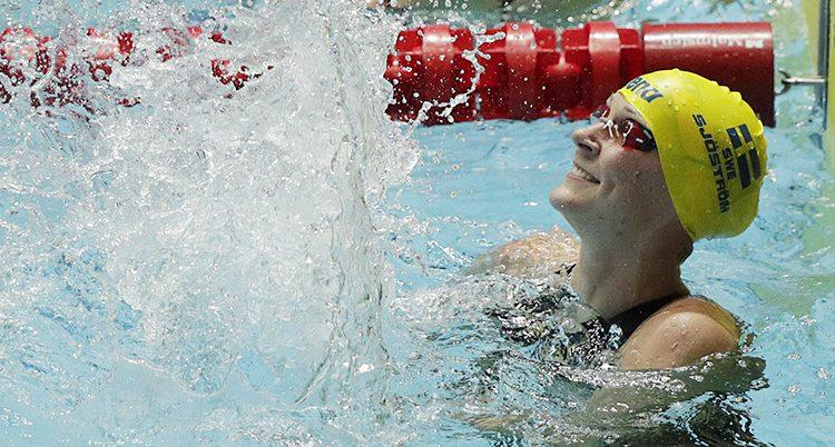 Sarah Sjöström har simmössa på sig och skätter glatt i vattnet