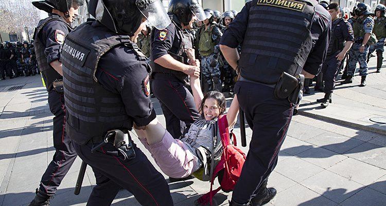 Fyra poliser bär en ung kvinna i benen och armarna