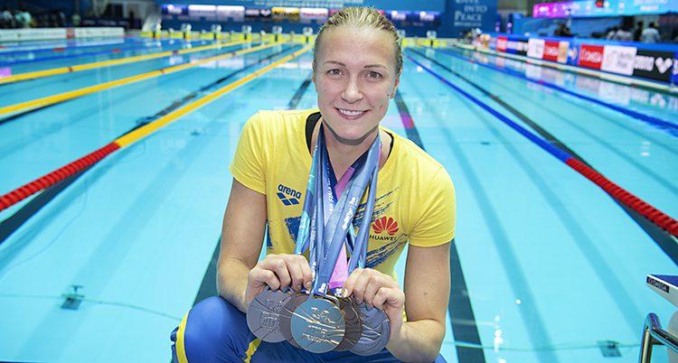 Simmaren Sarah Sjöström står vid en bassäng och visar sina fem medaljer.