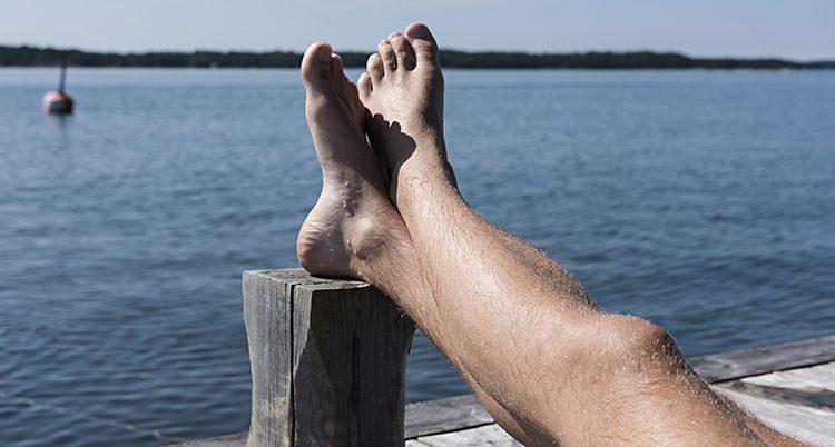En person ligger och solar på en brygga vid vatten. Bara benen syns i bilden.