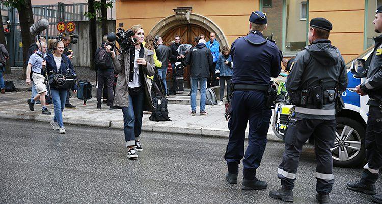 Poliser, en kvinna med kamera och andra människor utanför ett gult stenhus