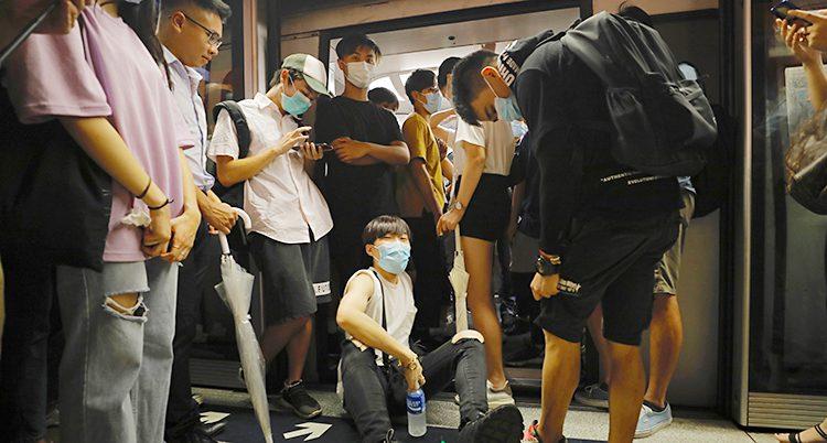Unga människor står och sitter framför dörren till ett tåg