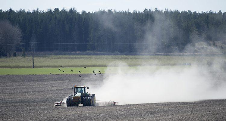 En traktor åker på ett fält.