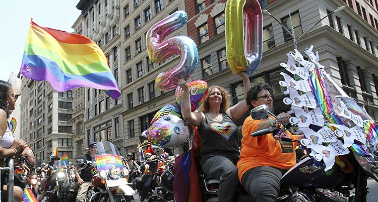 Två kvinnor på motorcykel, en håller i ballonger med siffrorna 50