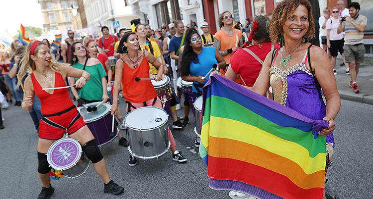 Kvinnor trummar och hålller i regnbågsflaggor