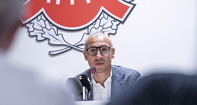 Henrik Larsson sitter vid en skrivbord bakom ett par mikrofoner. Han ser ledsen ut.