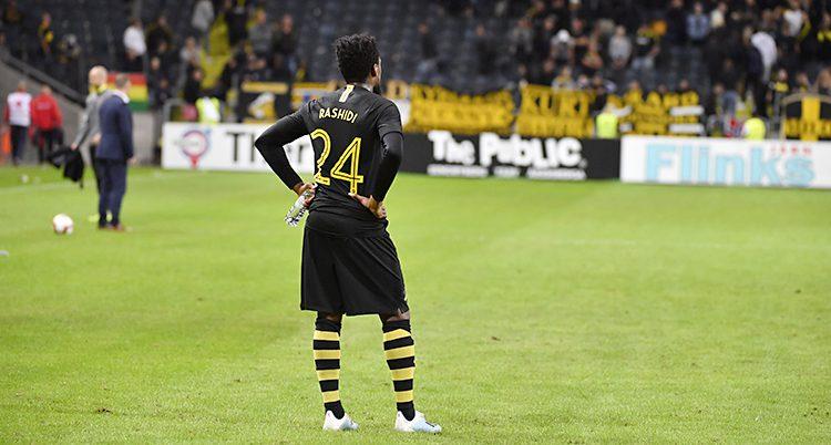 En spelare i AIK står på planen och deppar efter att matchen är slut. Han har svarta kläder med gula detaljer.