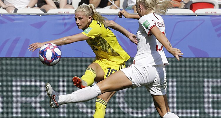 Sofia Jakobsson kämpar om bollen med en engelsk spelare i en match i fotboll.