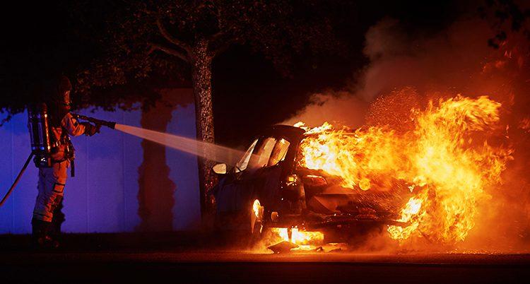 En brandman släcker en bil som brinner.