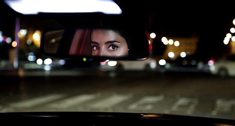En backspegel i en bil som är ute och kör på kvällen. Det är mörkt ute. En kvinnas ögon syns i backspegeln.
