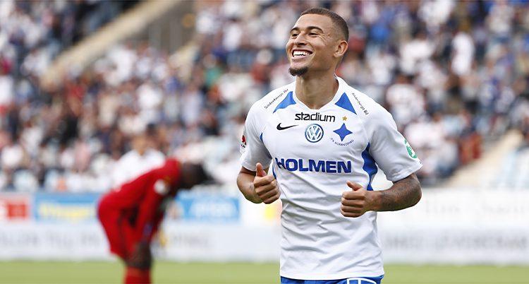 Jordan Larsson springer på en fotbollsplan och ler. Han har IFK Norrköpings tröja på sig.