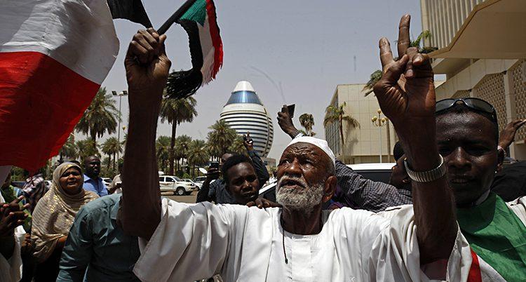 Folk är ute på en gata och firar. De lyfter händerna i luften och har Sudans flagga.