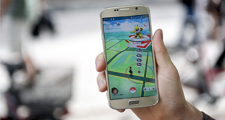En hand håller upp en mobile med Pokémon Go på skärmen