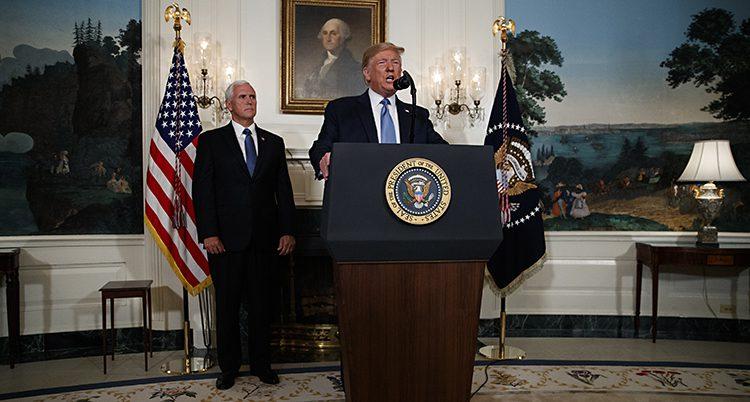 Donald Trump står i en talarstol med flaggor på båda sidorna.