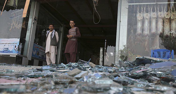 Två män står vid en affär i staden Kabul. På marken ligger en massa bråte efter en explosion.