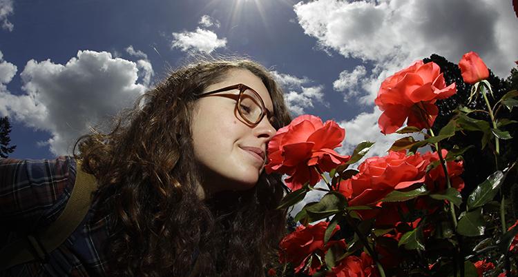 En kvinna med glasögon luktar på rosor i en park.
