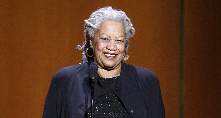 Toni Morrison ler. Hon står på en scen vid en mikrofon.