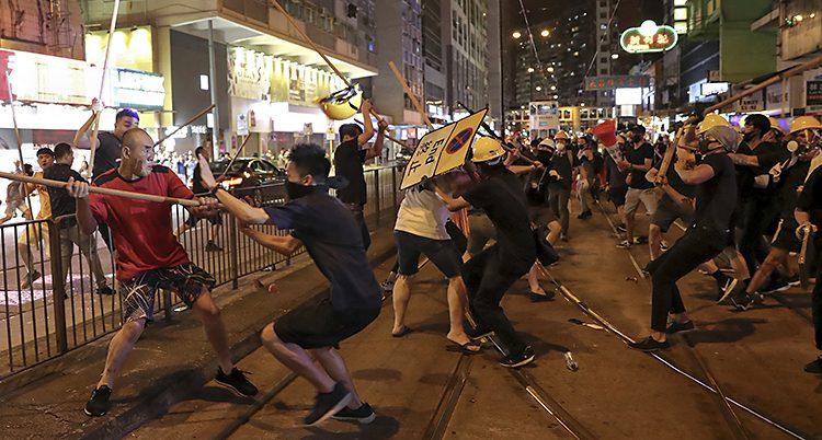 Många människor slåss mot varandra på en gata. Närmast i bild är två arga män. En har en käp som han ska slå med. Den andra håller upp händerna som skydd.