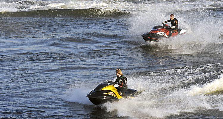 Två vattenskotrar som kör i full fart.-