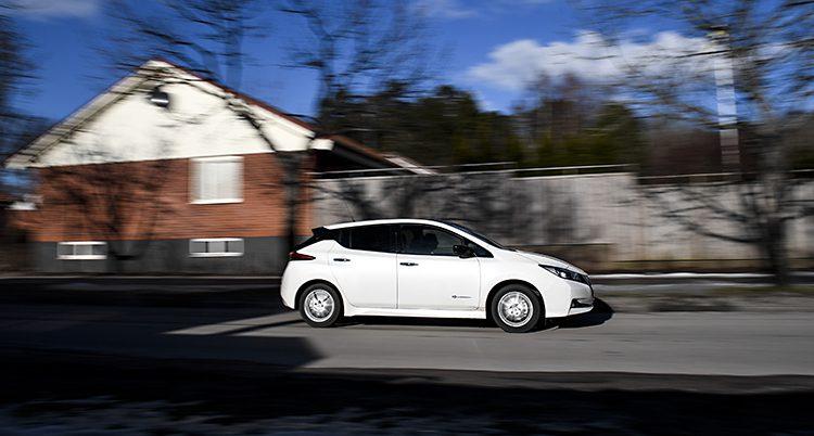 En bil kommer körande längs en gata i Sverige. Ett hus syns i bakgrunden.