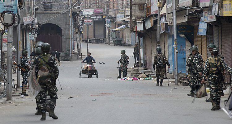 Flera soldater står längs en gata i staden Srinagar i Kashmir.