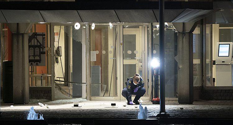Det är natt. En polis sitter på huk och undfersöker något på matken. Fönstren bakom är trasiga.