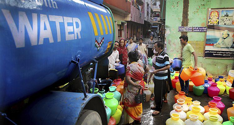 Människor vid en tankbil. De har med sig stora krukor i plast för att hämta vatten i.