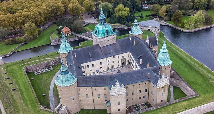 Flygbild över slottet. Det ligger på en ö och har flera torn och är byggt i fyrkant med innegård.