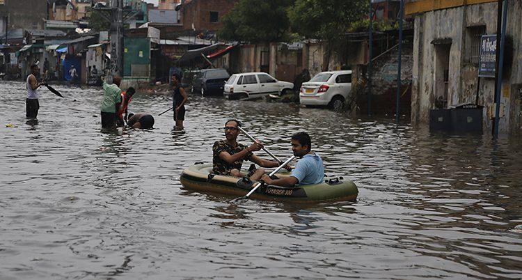Två män i en båt på en gatan som är helt översvämmad.