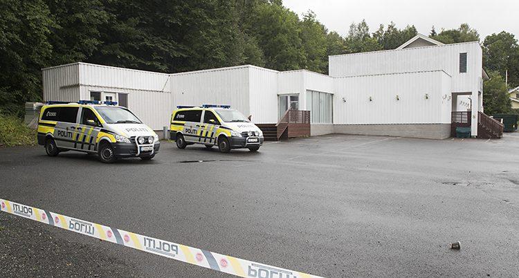 En vitt hus med två polisbilar utanför.