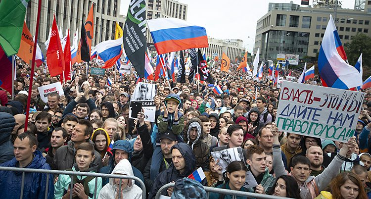 En gata fylld med folk med flaggor och skyltar.