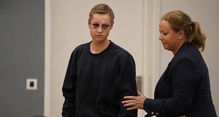 En ung man med blåtiror och små skador i ansiktet och en kvinna som visar honom var han ska gå.
